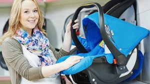 A woman is buying an infant safety seat