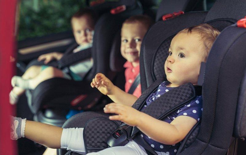Three children in car safety seat